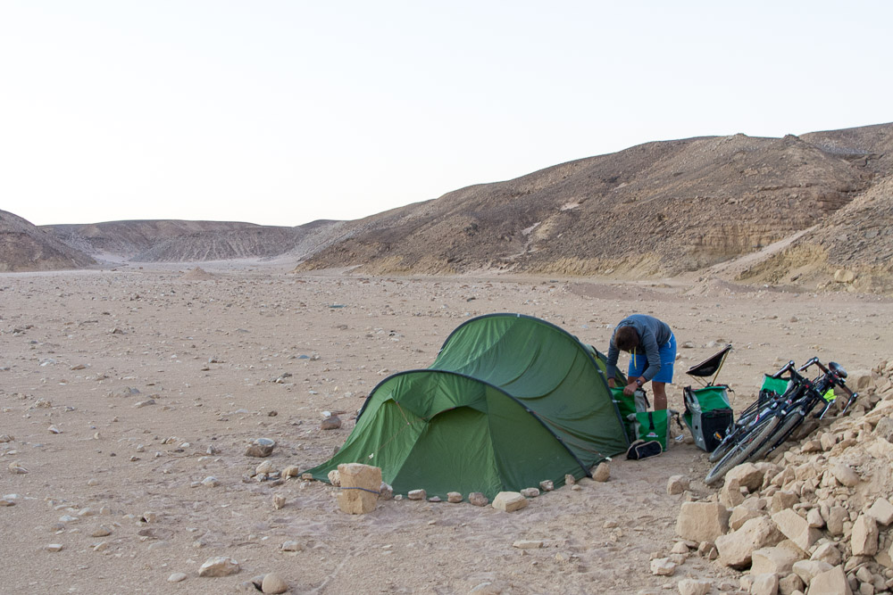 Taking the tent down after enjoying a peaceful night in the desert. Yes, we checked for snakes and scorpions!